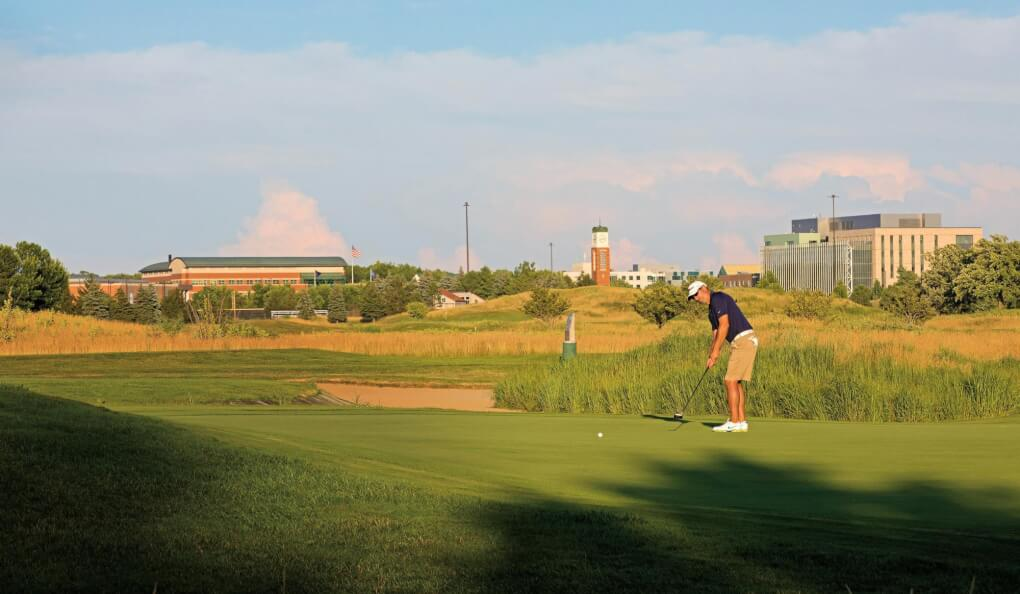 A golfer putts with a view of campus from the Meadows behind him.